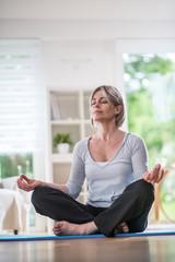 a pretty woman senior who does yoga at home, she meditates