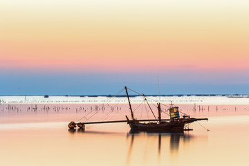 fishing boat used as a vehicle for finding fish in the sea.at sunset