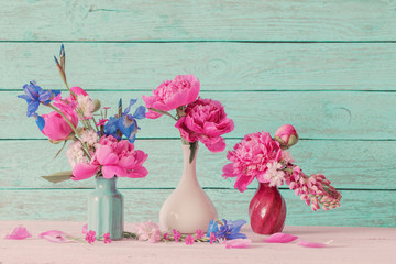flowers in vases on wooden background