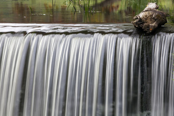 A calm waterfall with the piece of wood.