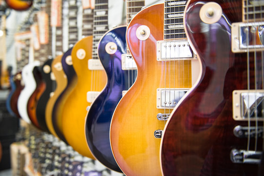 Many electric guitars body aligned in the store