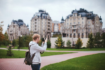 bearded man photographs the city