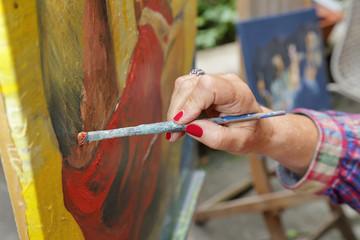 femme senior artiste peintre peignant peinture à l'huile en extérieur