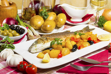 Fried sea bass with side dish on a plate, served on a table next to fresh vegetables, olives and cutlery.