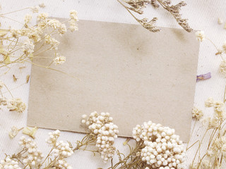 paper with dried flowers and space copy background top view