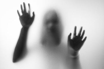Horror woman behind the matte glass in black and white. Blurry h Wall mural