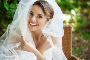 Young beautiful blonde bride in wedding dress and veil smiling.