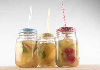 Three glass jars with colourful straws filled with fruit juice and pieces of cut up fruit. Taken on a white background.