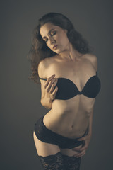 Sexy young woman body in black lingerie isolated on dark backgro