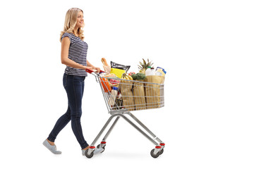 Woman pushing a shopping cart full of groceries