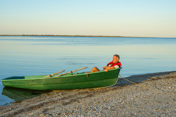 Man resting in a boat on the beach