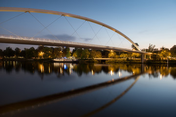 The modern High Bridge is nicely reflected in the smooth water of the Meuse river.