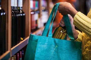 Woman putting wine bottle in bag