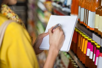 Woman at grocery section writing in notepad