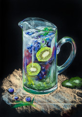 Glass transparent jug of lemonade from kiwi and forest fruit ice