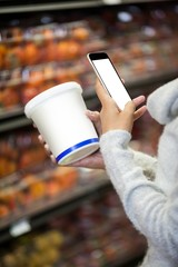 Woman using mobile phone while shopping for grocery