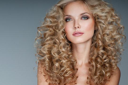 Beautiful blonde woman. Healthy Long Blond Hair. Curly Hair.   B