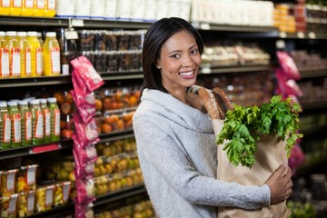 Portrait of smiling woman holding a grocery bag