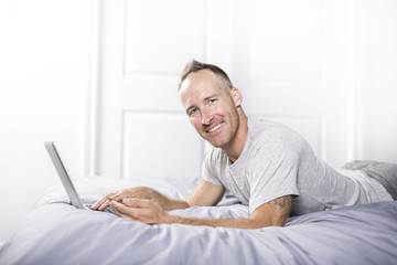 Serious casual young man using laptop in bed at home