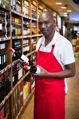 Portrait of male staff arranging wine bottles on shelf