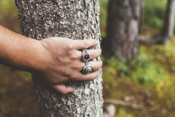 Hand with rings leaning on tree in a forest