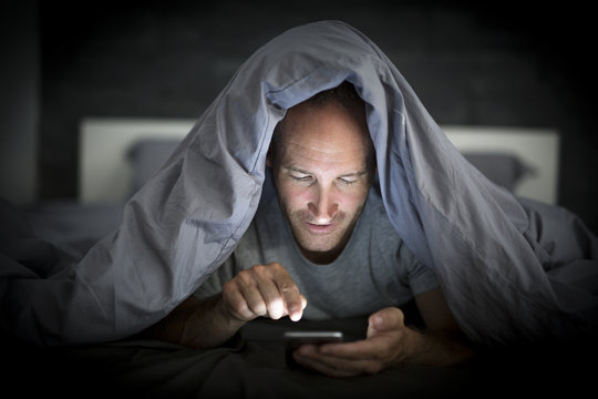 young cell phone addict man awake late at night in bed using smartphone