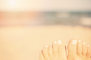 Holiday concept. Woman feet close-up relaxing on beach, enjoying sun and splendid view. Sandy feet on the beach. Sun, sun haze, glare