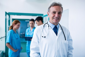 Portrait of smiling doctor standing in corridor