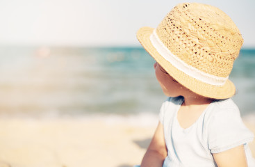 Baby girl child with straw hat and blue dress looking at the sea on a sunny day. Little girl sitting back on the shore of the sea. Sun, sun haze, glare