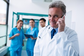Portrait of smiling doctor talking on mobile phone in corridor