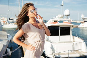 Young beautiful girl in suglasses standing at the sea pier
