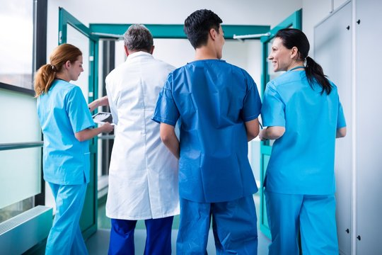 Rear view of doctor and surgeons interacting with each other