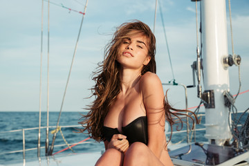 Close up portrait of girl in swimsuit posing on yacht