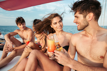 Group of friends drinking and having party on sailing boat