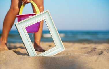 Wooden picture frame on the beach sand, summer concept. Children play in the sand beach