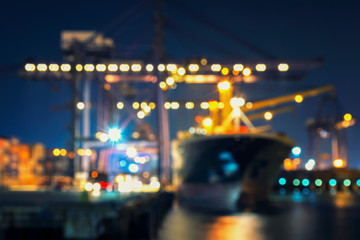 Blur bokeh of harbor with large ship and crane at night.