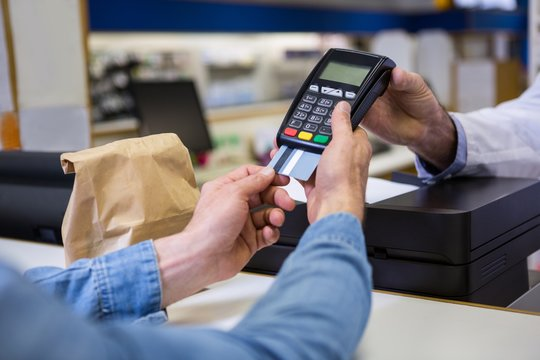 Customer entering pin in payment terminal machine