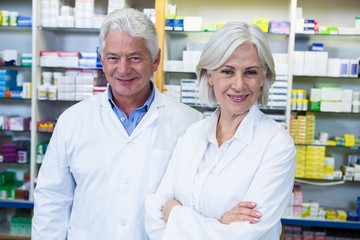 Smiling pharmacists standing in pharmacy