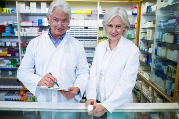 Pharmacists checking and writing prescription for medicine