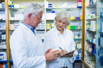 Pharmacists checking and writing prescription