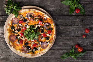 Pizza with onions , black olives , peppers , mushrooms on the wo