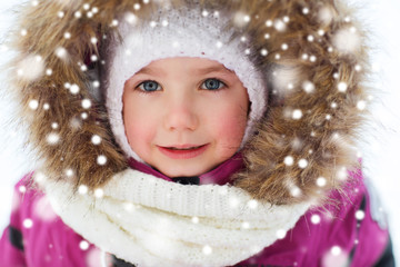 face of happy little kid or girl in winter clothes