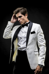 Success, elegant man in a white suit tuxedo with bow tie around