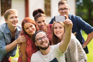 friends taking selfie by smartphone at summer
