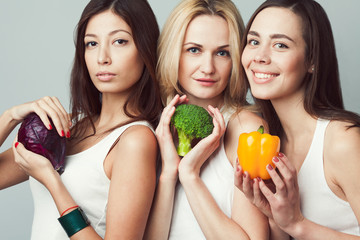 Raw, living food, veggie concept. Portrait of three happy young women