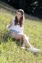 Mädchen sitzt in Wiese im Sommerurlaub