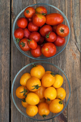 Yellow and red tomatoes on wooden surface