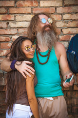 portrait of happy couple of hippie against background of a brick