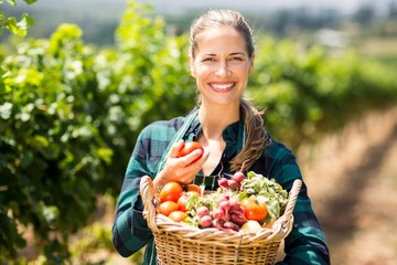 Portrait of happy female farmer holding a basket of vegetables