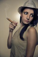 sensual woman with shiny hat smoking a cigar
